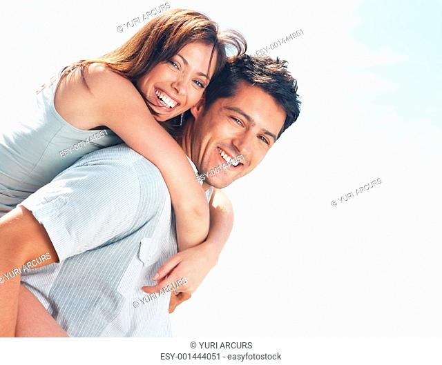 Portrait of a happy young girl enjoying piggyback ride on her boyfriend back - Outdoor