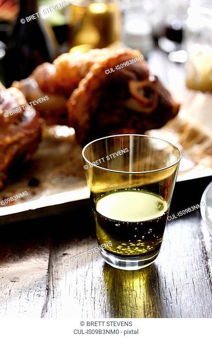 Pork hock on platter, sparkling drink in foreground, close-up