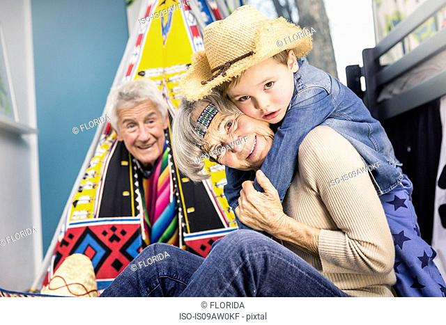 Portrait of senior couple and grandson wearing cowboy hat on living room floor