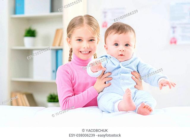 My little brother. Positive cheerful little girl holding infant and smiling while expressing positivity