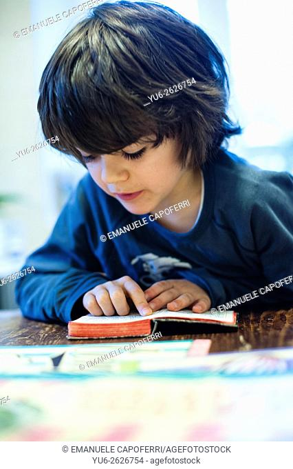 Child sitting at the kitchen table reads the book of prayers in Latin
