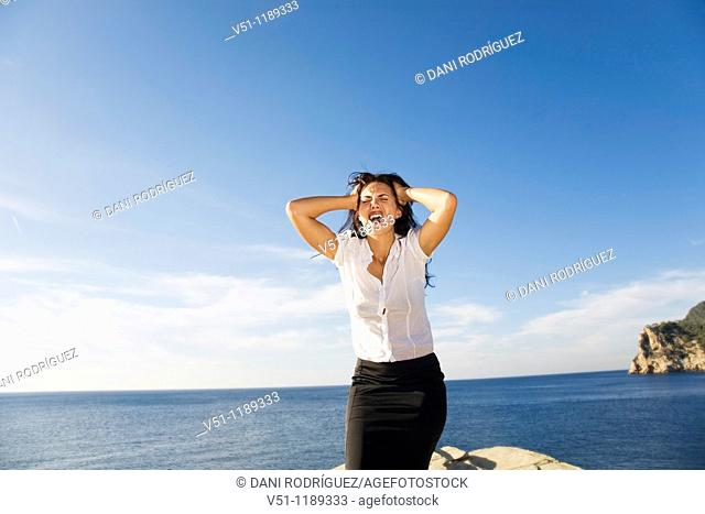 Brunette woman screaming in a rock by the sea