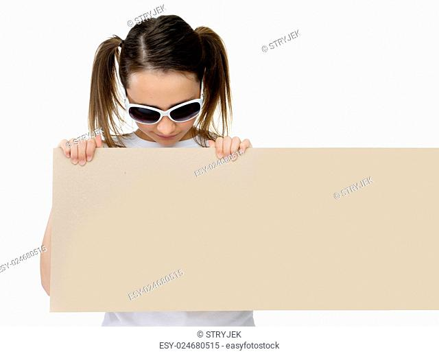 Trendy young girl in stylish sunglasses pointing to a blank card or sign that she is holding in front of her chest with copyspace for your text or advertisement