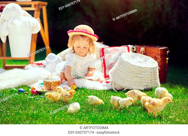 Cute little smiling baby girl in park on green grass. Poster for Easter holiday. Selective focus on chicken