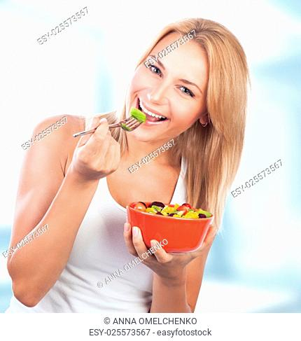 Portrait of pretty blond woman eating fresh tasty fruit salad on the kitchen at home, special fruity diet, enjoying organic nutrition and healthy lifestyle