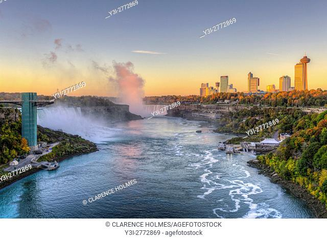 A view of the Niagara River including the American Falls, Horseshoe Falls, and skyline of Niagara Falls, Ontario in golden light just after sunrise