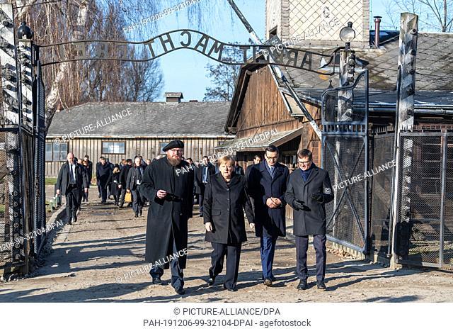06 December 2019, Poland, Oswiecim: Federal Chancellor Angela Merkel (CDU) visits the former German Auschwitz concentration camp and walks under the entrance...