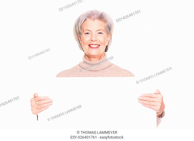 smiling senior woman with a blank advertising sign against white background