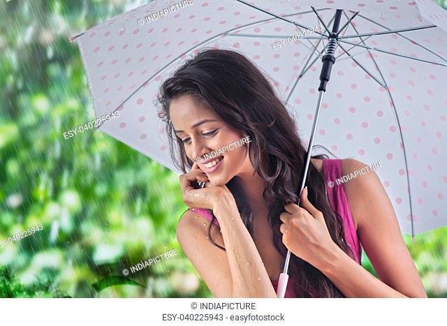 Woman with umbrella enjoying the rain