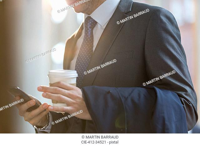 Close up businessman in suit with coffee texting with cell phone