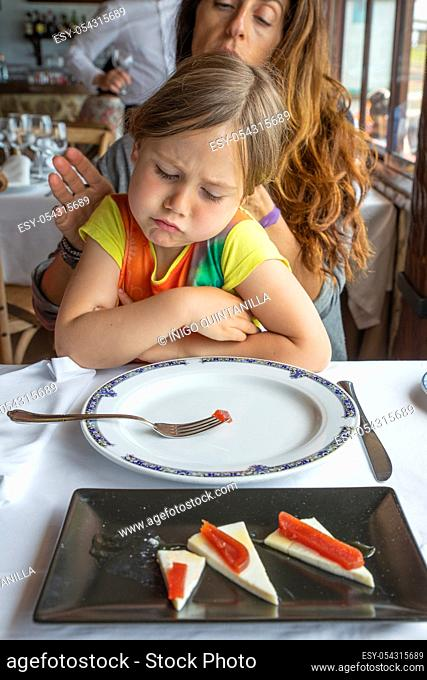 portrait of four years old blonde little girl looking with disgust at a piece of quince on a fork sitting on mother legs in restaurant