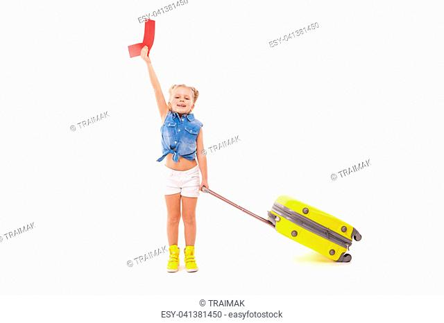 Isolated on white, pretty caucasian blonde girl in blue shirt, white shorts, sunglasses and yellow boots hold yellow suitcase by the handle, look at camera