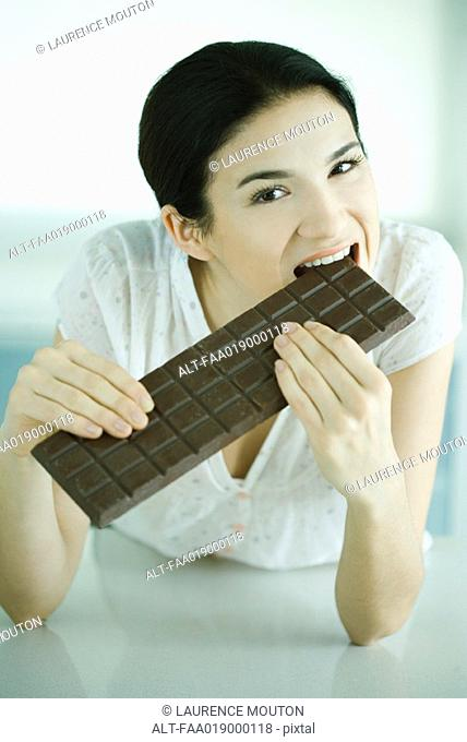 Woman biting into large bar of chocolate