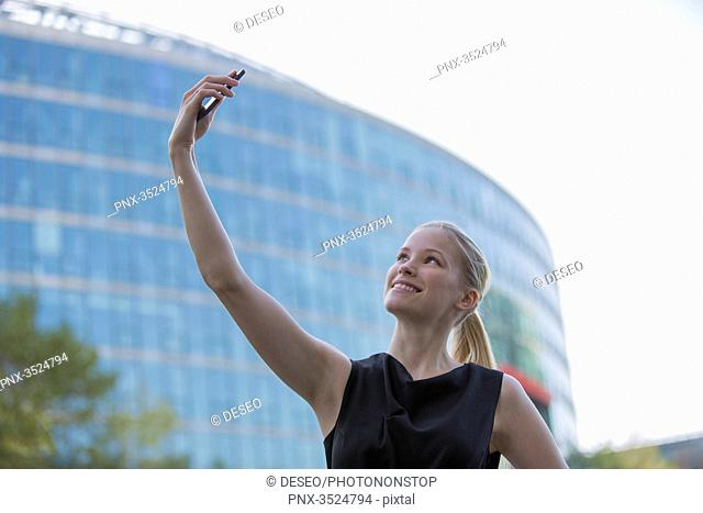 Pretty young woman taking a selfie in front of an Office Building