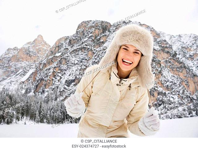 Portrait of cheerful young woman in fur hat in winter outdoors