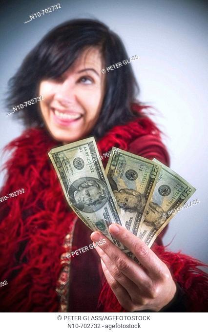 Woman holding three American twenty dollar bills