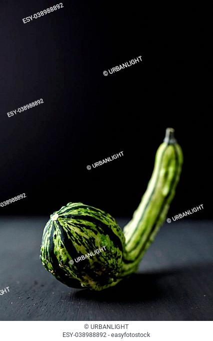 Organic miniature gourds on black background