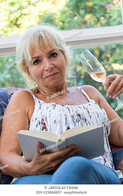 Senior mature blond woman is sitting on a couch and she is holding a glass of champagne in the left hand and book in the right hand