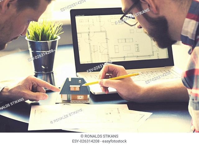 architect showing new family house model to customer at office