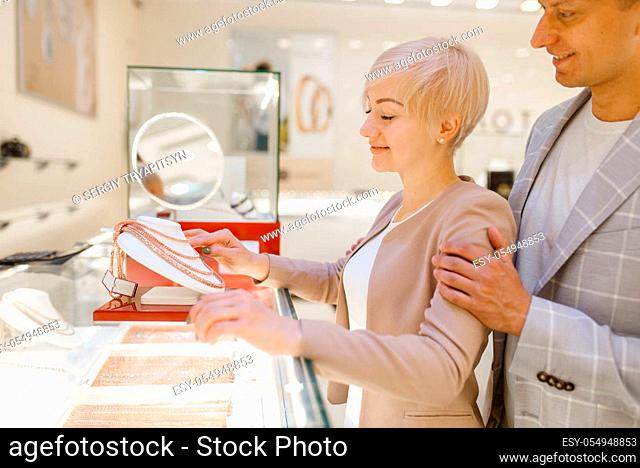 Love couple choosing gold chain. Male and female customers looking on jewels in jewelry store. Man and woman buying golden decoration