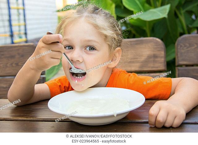 Five-year girl sits at a table on the veranda and enjoy eating porridge