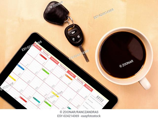 Tablet pc showing calendar on screen with a cup of coffee on a desk