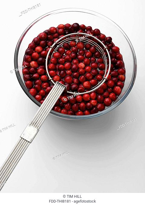 Cranberries in a bowl with a metal strainer