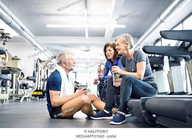Group of fit seniors in gym resting after working out