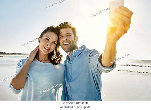 Portrait of happy couple taking selfie on the beach with smartphone