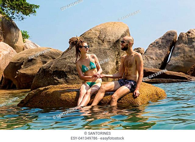 Cheerful couple sitting on a large stone in the sea