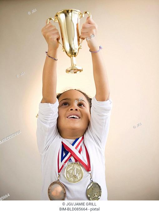 African American girl holding up trophy