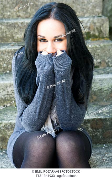 Young woman is smiling, she is warming her hands in long sleeves