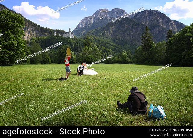 12 June 2021, Bavaria, Schwangau: A bride and groom from China pose for wedding photos on a meadow in front of Neuschwanstein Castle