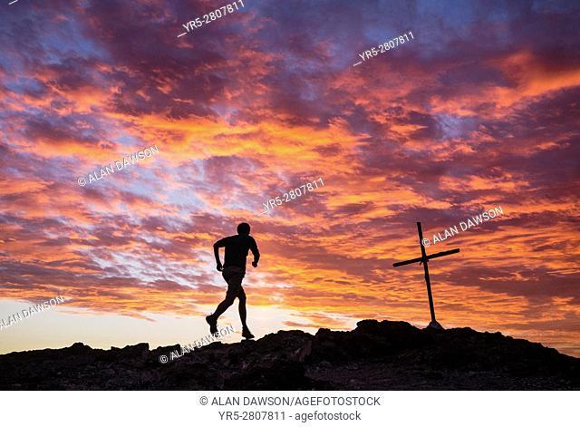 Mature runner on mountain overlooking Las Palmas city on Gran Canaria at sunrise. La Isleta, Las Palmas, Gran Canaria, Canary Islands, Spain