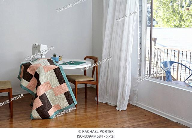 Quilt in sewing machine on table by window