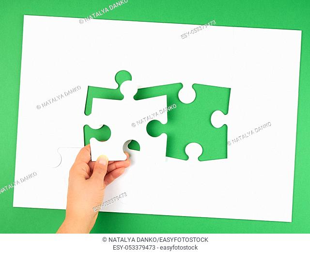female hand puts empty white big puzzles on a green background, top view