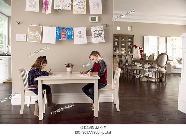 Brother and sister drawing with crayons at living room table