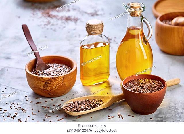 Brown flax seeds in wooden plate and flaxseed oil in glass bottle on brown rustic wooden background, top view, close-up, selective focus