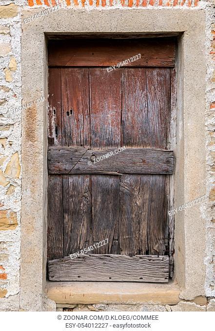 Old wooden and crooked door in Montechiaro d'Acqui, Piedmonte, Italy