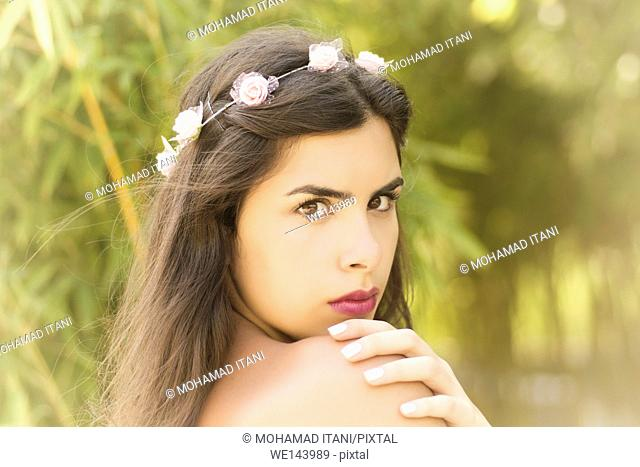 Serious beautiful woman hand on shoulder looking away outdoors