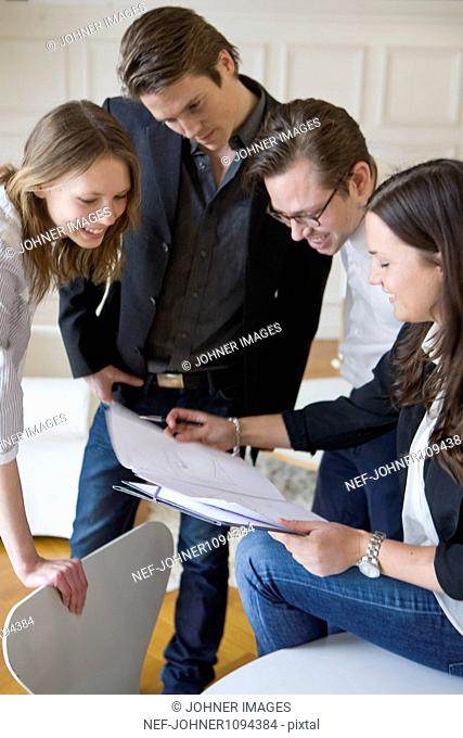 Group of young businesspeople smiling over documents