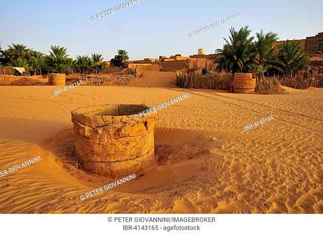 Fountain in a dry riverbed, Wadi or Oued, in the evening light, Chinguetti, Adrar Region, Mauritania
