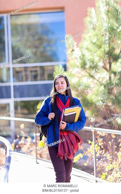 Mixed race student holding books on campus