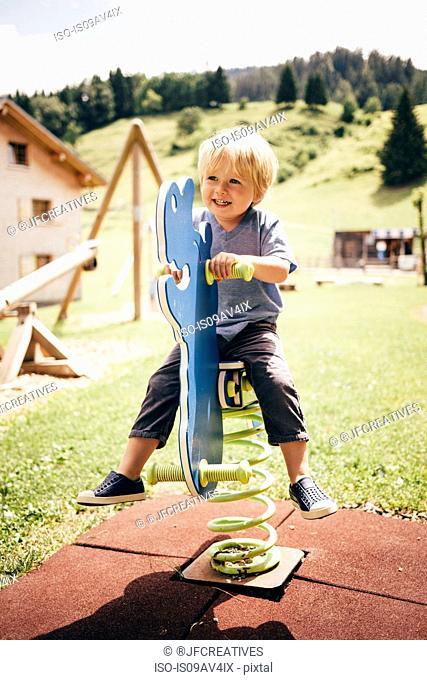 Boy in playground sitting on spring rider looking away smiling, Bludenz, Vorarlberg, Austria