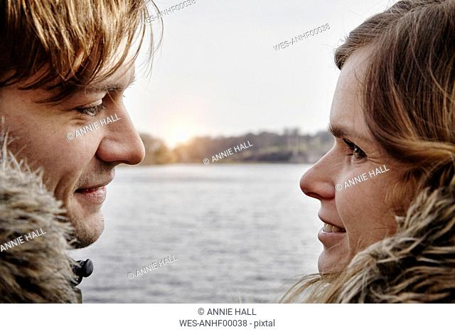 Germany, Potsdam, young couple at Havel River face to face
