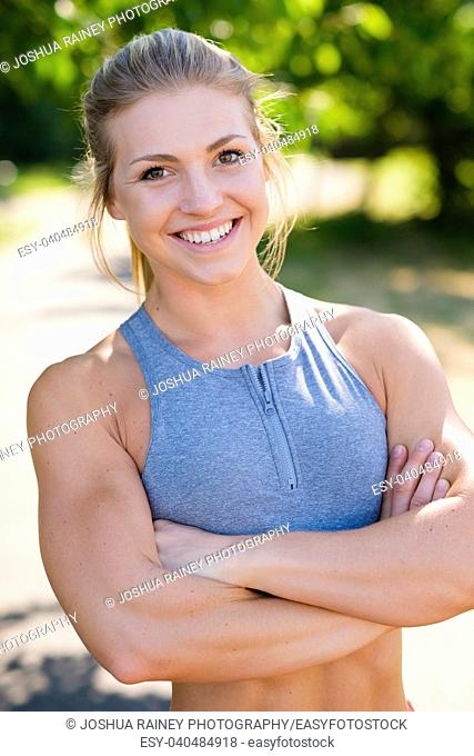 Post workout fashion portrait of a young female athlete while working out on an outdoor track in the summer