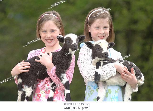 twins holding twin lambs