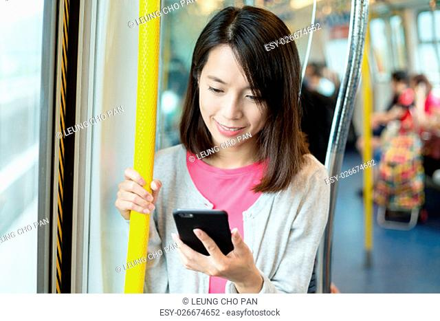 Woman using cellphone inside compartment
