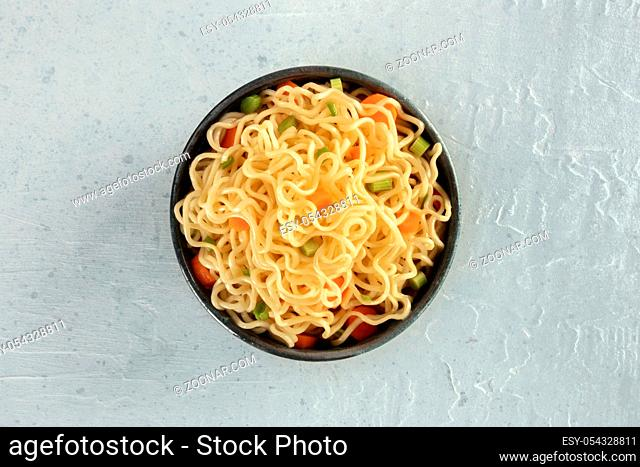 Instant noodles with carrot and scallions, vegetable soba bowl, shot from the top
