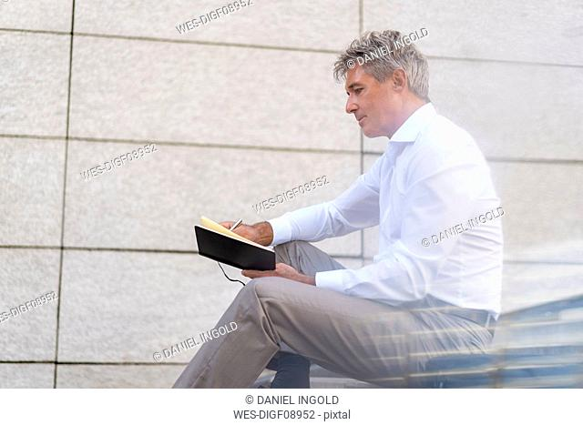 Mature businessman sitting on stairs looking at notebook